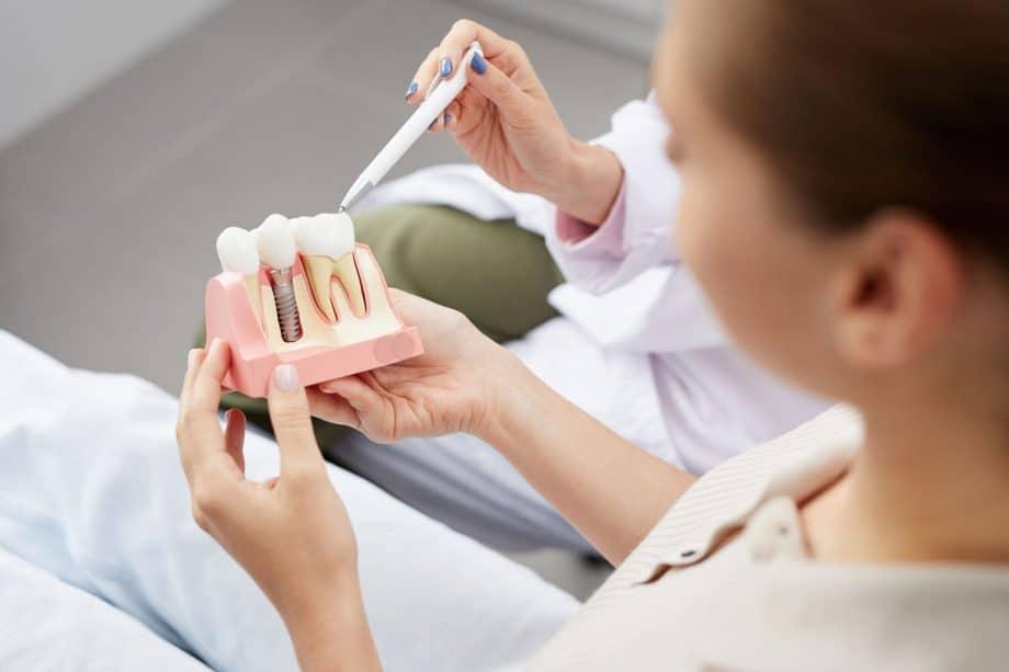 dental patient holding model of dental implants