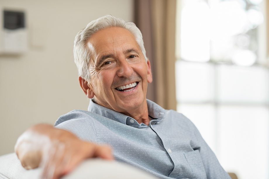 senior man on couch, smiling