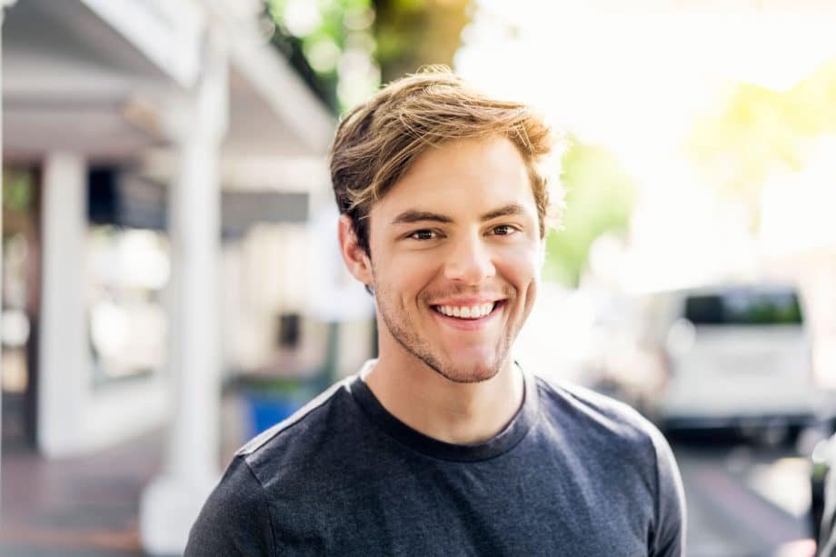 young man standing on sidewalk, smiling